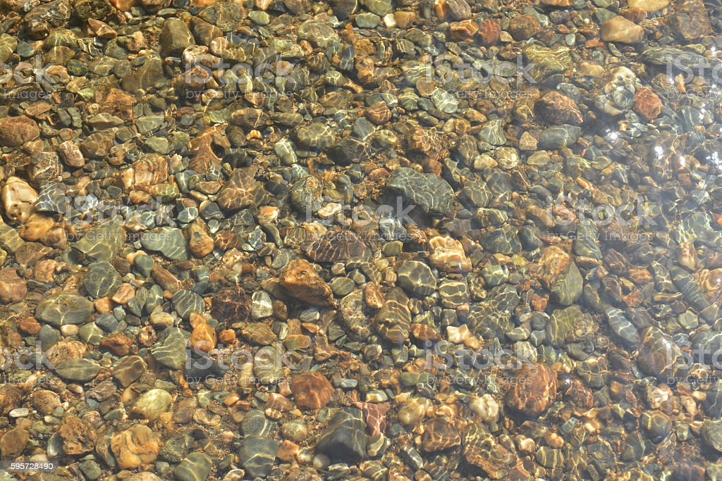 Background of river pebbles under the clear water. stock photo