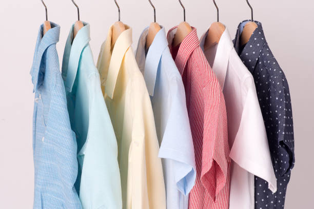 background of shirts hanging on hanger - menswear stock photos and pictures