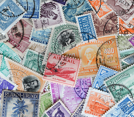 Colorful collection of old stamps spread out and overlapping on a flat surface.
