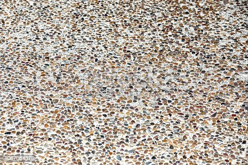 This is a photograph of a textured pebble sidewalk background. The focus is on the foreground and fall slightly off towards the back. The pebbles are tiny and small and multicolored.