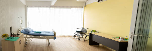 Background of the patient room with a wheelchair, bed and the light from the window. Panorama patient room stock photo