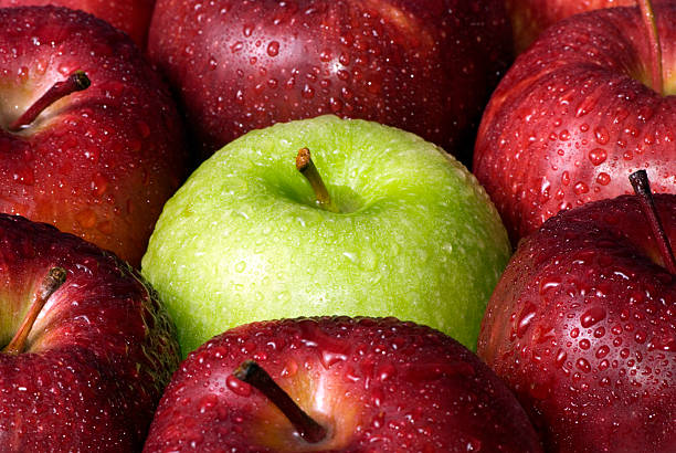 Background of wet red apples with one wet green in middle stock photo
