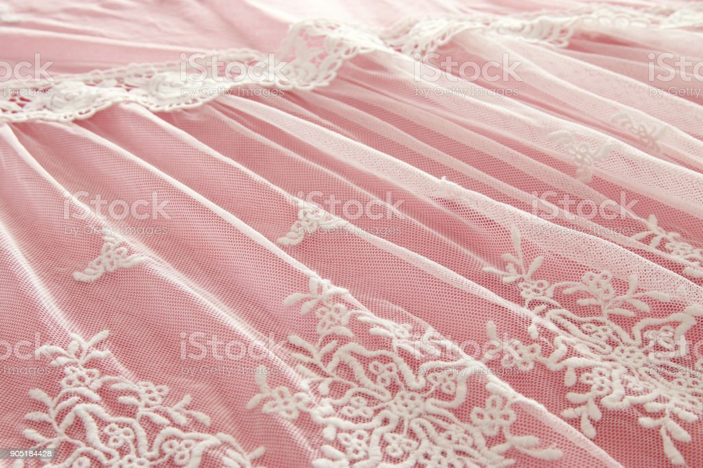 Background of white delicate lace fabric over pink background. stock photo