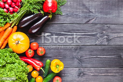 istock Background of wooden  black planks with fresh vegetables. 492983984