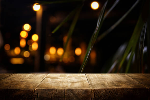 background of wooden table in front of abstract blurred restaurant lights – zdjęcie
