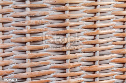 Part of the sidewall of the wooden wicker laundry basket wall with textile bag inside close-up, background