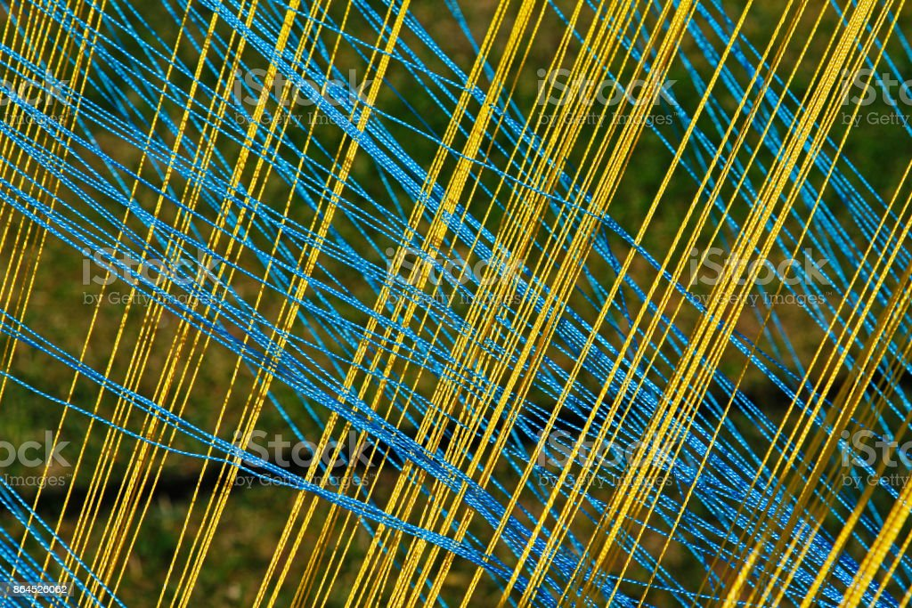 Background of yellow and blue thread intersecting diagonally stock photo