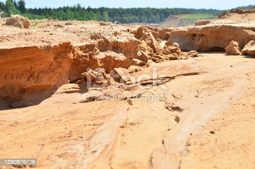 Background of yellow sand with small stones after rain. Soil erosion after heavy rainfall and precipitation. Texture of scattered sand fine gravel