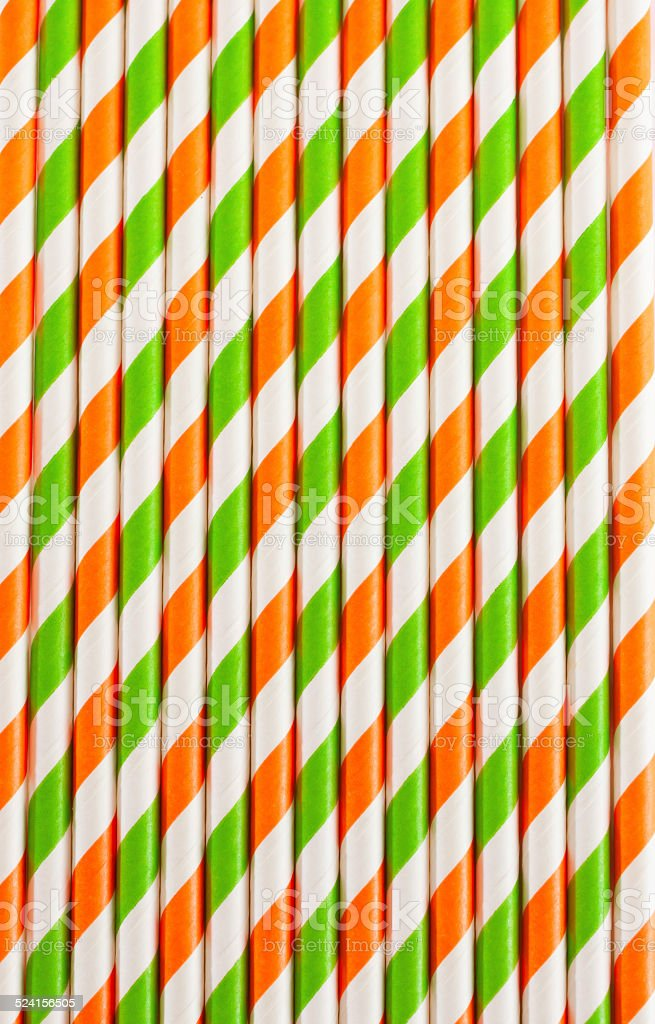 Halloween background of striped drinking straws in orange and green...