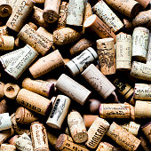 Used wine corks on sackcloth background with empty space for text. Colorful corks from white and red wine bottles