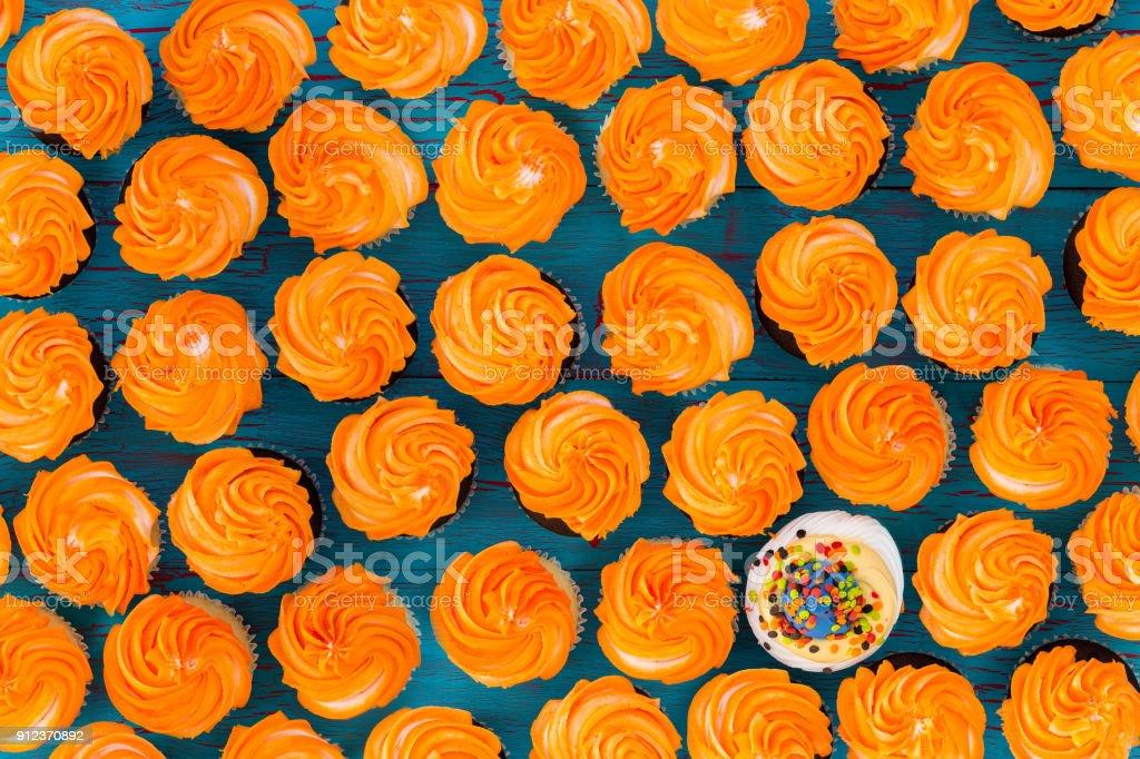 Background pattern of glazed orange cupcakes stock photo