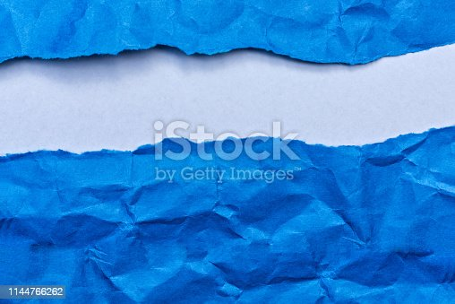 A blue background of wrinkles ripped.