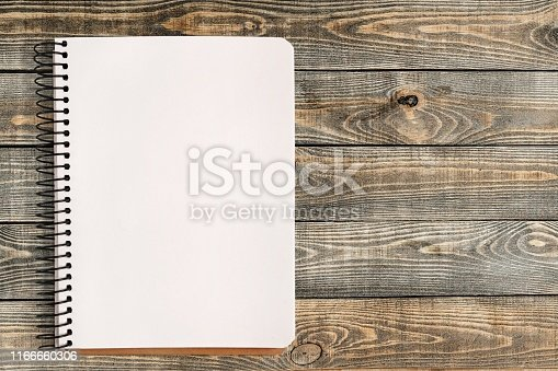 Spiral notebook with blank page on wooden table