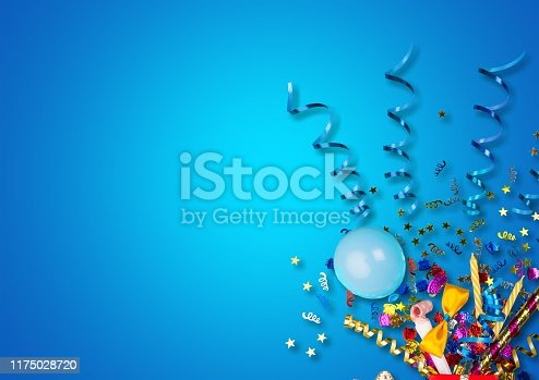 Colorful balloons and confetti on blue table