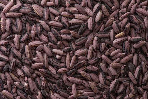 909806032 istock photo Background raw dark red purple rice, close up 949097806