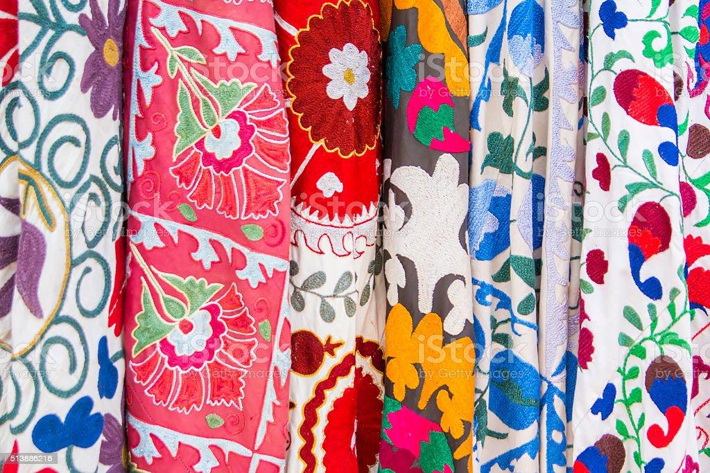 background set of embroidered fabrics on the market stock photo