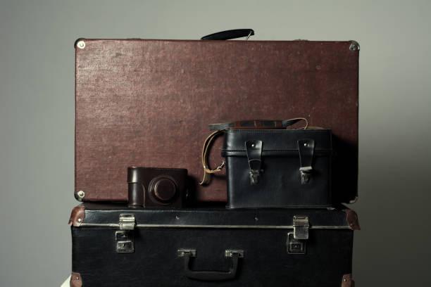 background stack of old shabby suitcases and the camera - nachrichten video stock-fotos und bilder