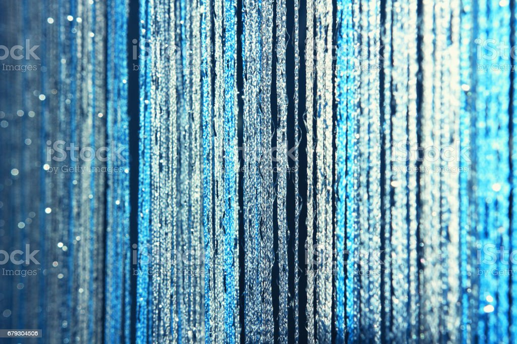 Background texture curtains made of blue threads with glitter and blur at the edges. stock photo