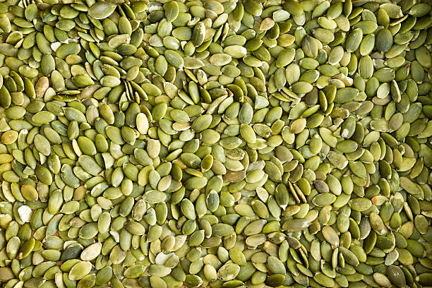 Background texture of green hulled pumpkin seeds stock photo