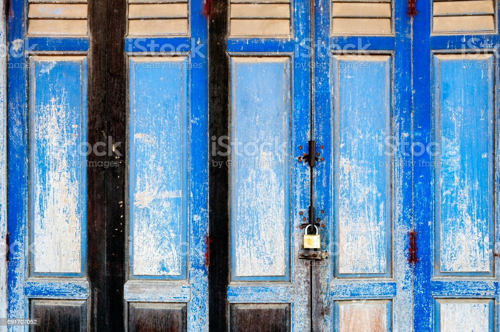 Background texture on old rustic blue wooden folding door of classic Sino-Portuguese architectural style shophouse building stock photo