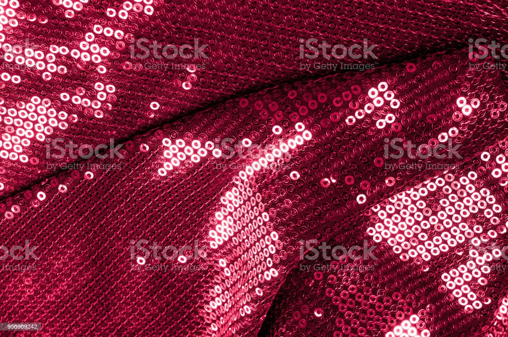 Background texture, pattern. Cloth red maroon with paillettes. Look at these Neon Pink Paillette Sequins. Round neon pink paillette sequins overlap with an iridescent sheen across a sheer purple mesh stock photo