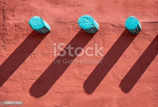 Background - Turquoise corbels and their long shadows on an orange stucco wall on southwestern style building
