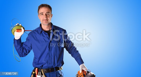 Background with uniformed electrician with tools and electrical equipment and blue background. Front view. Half body