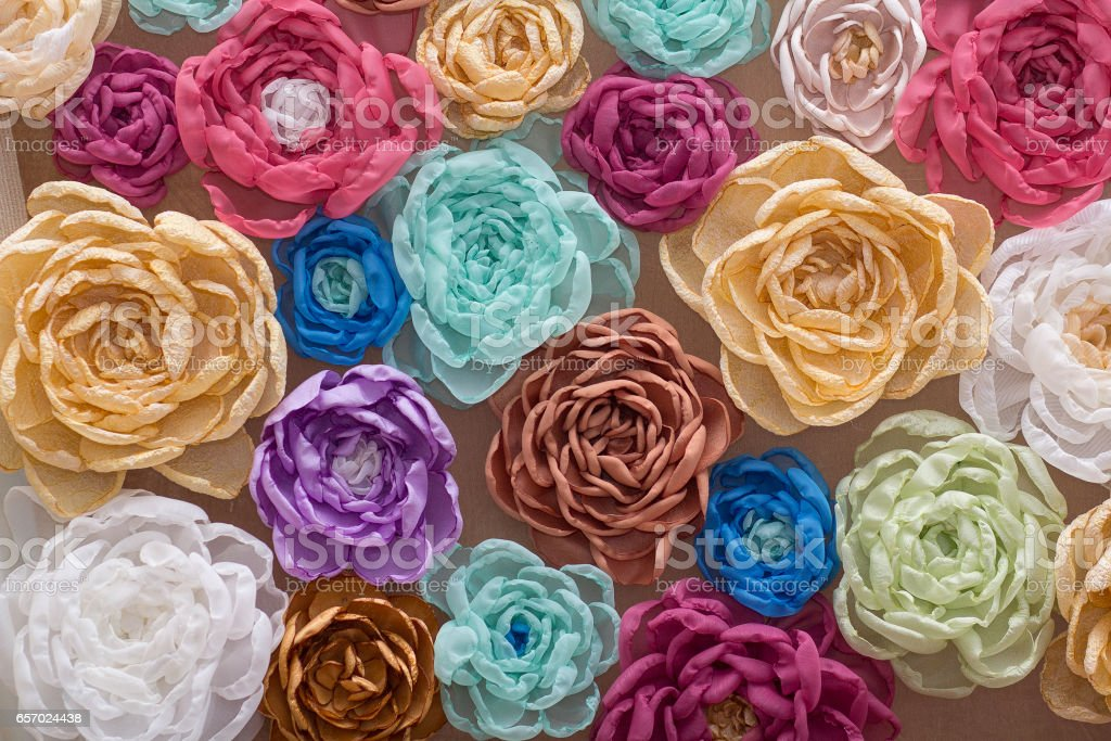 Background with a lot of colorful artificial flowers