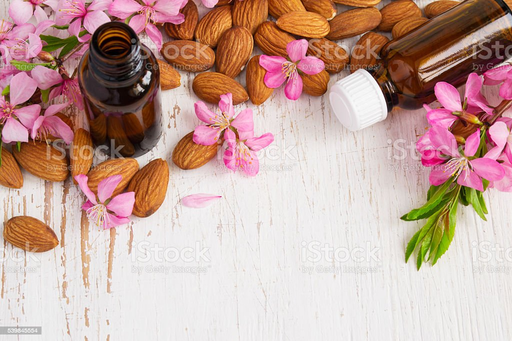 Background with almond oil, almonds and flowers. stock photo