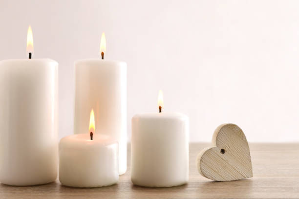 Background with burning candles and heart on wooden table stock photo