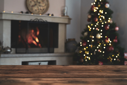 Empty wooden table with beautiful Christmas decoration in background and luxury fireplace.