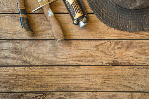 Background with hunting knives and hat on wooden planks. Space for text, top view