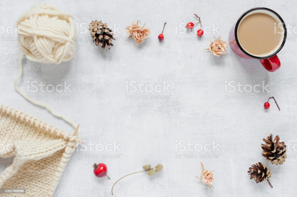 Background with knitting, red mug with hot drink and decoration on...