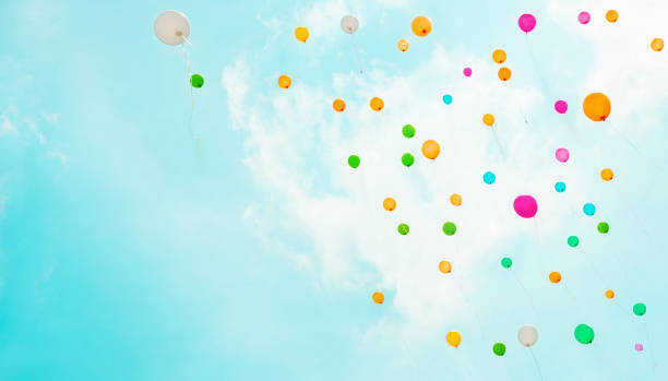 Background with multicolored flying balloons in blue sky stock photo