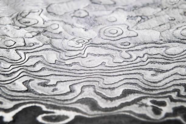 hintergrund mit muster aus damaststahl. close up. macro-schuss einer damaskus-stahlmessermesserklinge textur. damaskus stahlmuster. metall-und stahlhintergrund. damaskus stahl mit originellem muster. - damaststahl stock-fotos und bilder