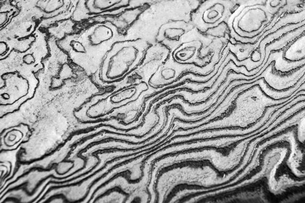 hintergrund mit muster aus damaststahl. zusammenrücken. makro-aufnahme einer damaskus messer klinge textur. damaskus stahlmuster. metall und stahl hintergrund. damaskus stahl mit original muster. schwarz und weiß - damaststahl stock-fotos und bilder