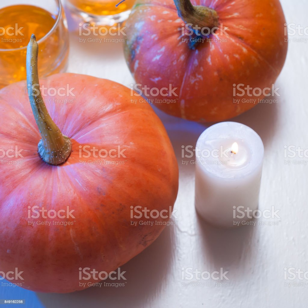 Background with pumpkins and candle on white wooden table stock photo