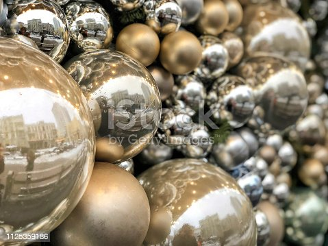 istock background with shiny silver and golden balls with reflection of street 1125359186