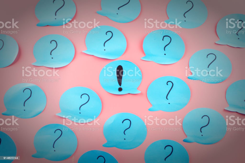 question marks written on blue papers exclamation point in the center