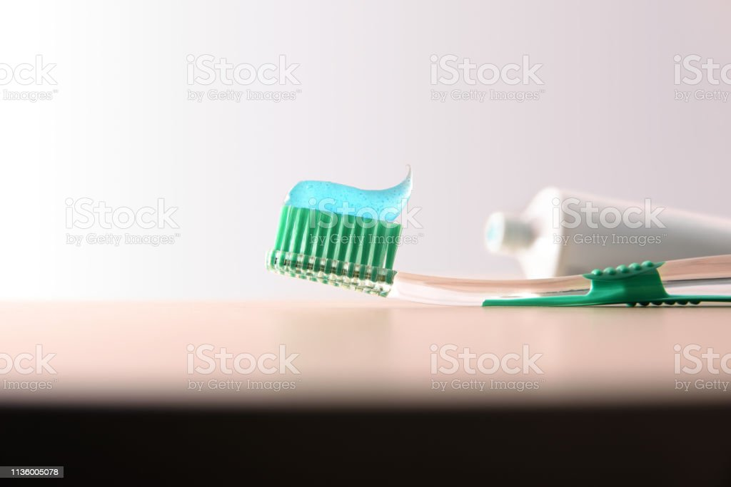 Background with toothbrush and toothpaste on wooden table front view stock photo