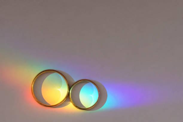 Hintergrund mit zwei Eheringen mit Regenbogen. – Foto