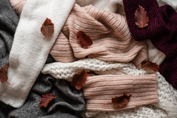background with warm sweaters. pile of knitted clothes with autumn leaves, space for text, autumn winter concept. copy space. - caxemira imagens e fotografias de stock