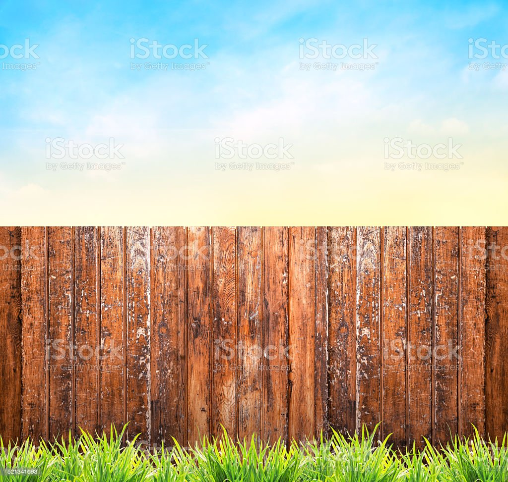 Background with wooden fence , grass and blue sky stock photo