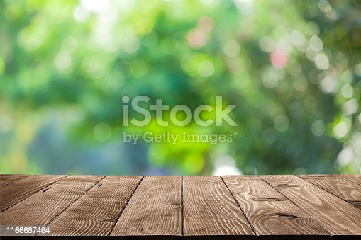 Empty rustic wooden table with defocused green lush foliage at background. Ideal for product display on top of the table. Predominant color are green and brown. DSRL studio photo taken with Canon EOS 5D Mk II and Canon EF 100mm f/2.8L Macro IS USM.