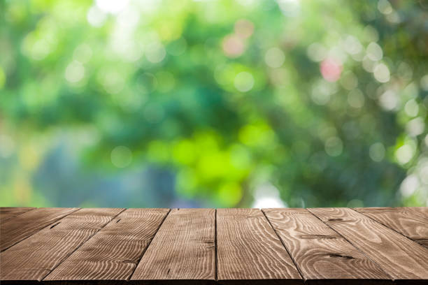 backgrounds: empty wooden table with defocused green lush foliage at background - woodland stock pictures, royalty-free photos & images