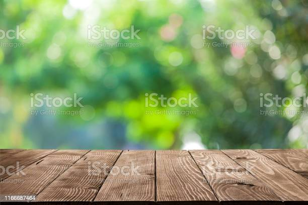 Photo of Backgrounds: Empty wooden table with defocused green lush foliage at background