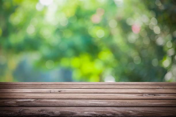 Hintergrund: Leerer Holztisch mit defokussiertem grünem Laub im Hintergrund – Foto