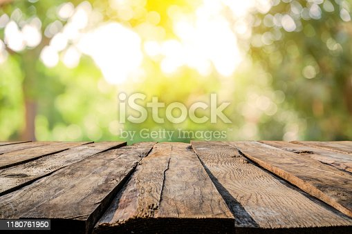 Empty rustic wooden table with defocused yellowish lush foliage at background. Ideal for product display on top of the table. Predominant color are green and brown. XXXL 42Mp outdoors photo taken with SONY A7rII and Zeiss Batis 40mm F2.0 CF