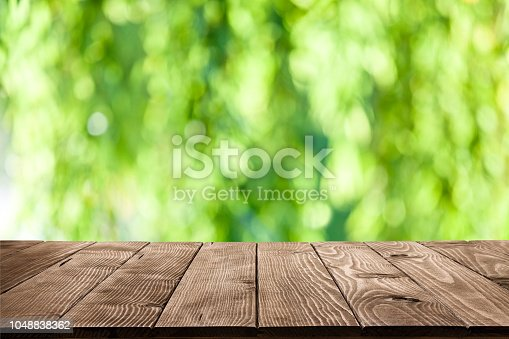 1048926386istockphoto Backgrounds: Empty wooden table with green lush foliage at background 1048838362