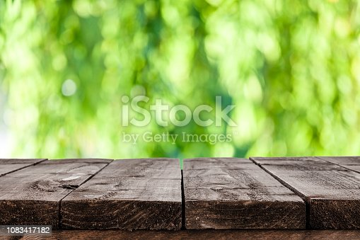 Empty rustic wooden table with defocused lush foliage at background. Ideal for product display on top of the table. Predominant color are green and brown. DSRL studio photo taken with Canon EOS 5D Mk II and Canon EF 100mm f/2.8L Macro IS USM.